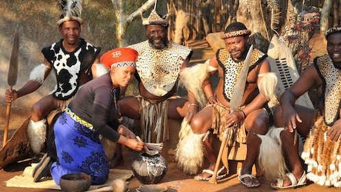 Men dressed in traditional clothing are served Zulu beer by woman in Shakaland