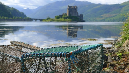 Crab pots on shore with Scottish castle in background