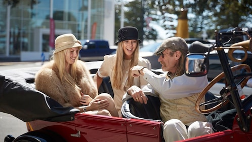 Tour guide talking with guests in vintage car and clothing in Napier