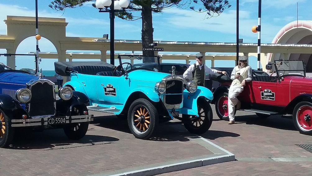 Show item 5 of 5. Tour guides waiting near vintage convertible in Napier