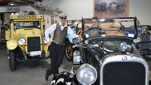 Tour guide with tourist in car at Hooters Vintage and Classic Vehicle Hire garage in Napier