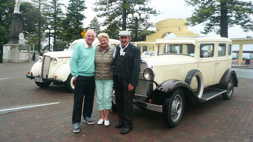 Tourist with tour guide stand in front of vintage cars in Napier