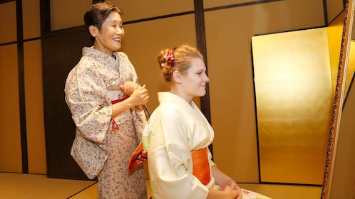 Woman being dressed for a tea ceremony
