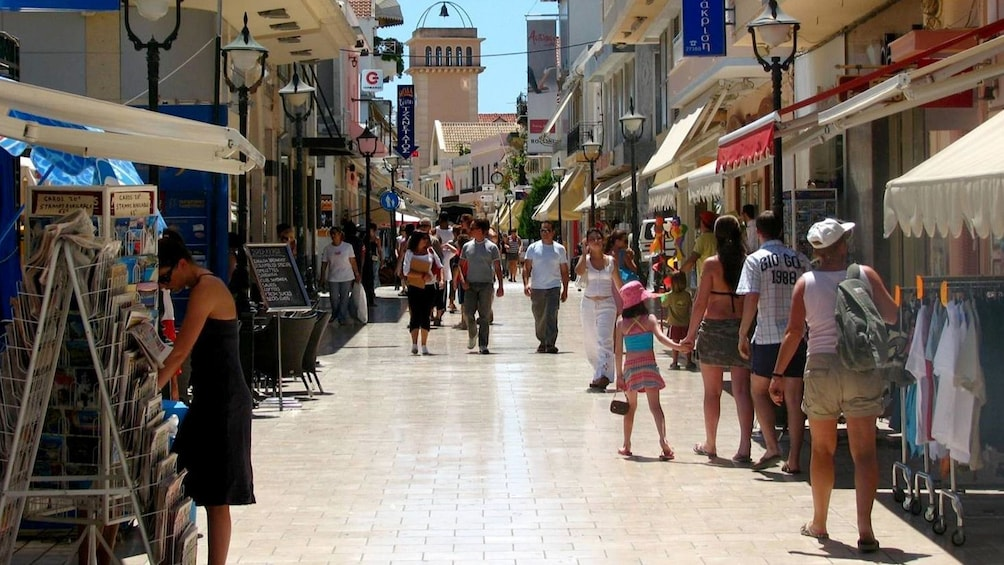 Show item 3 of 5. Shoppers and tourists on a street on Kefalonia Island