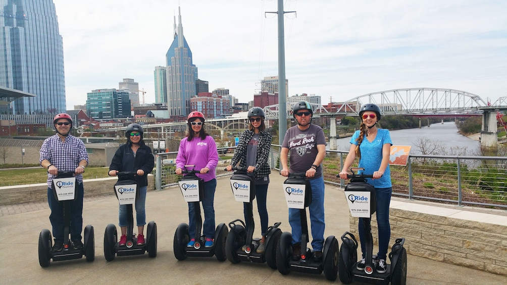 Group poses on segways with bridge and skyline in background for tour in Nashville