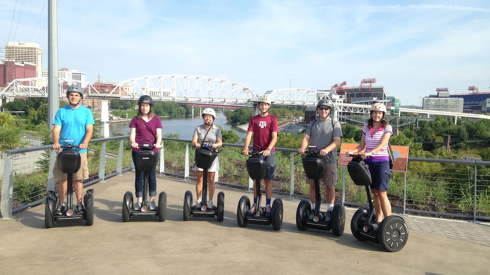 Group poses on segways with bridge in background for segway tour in Nashville