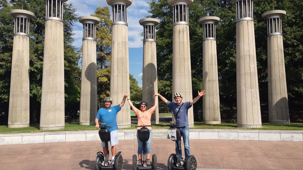 Three segway riders pose for photo in front of columns in park on tour of Nashville