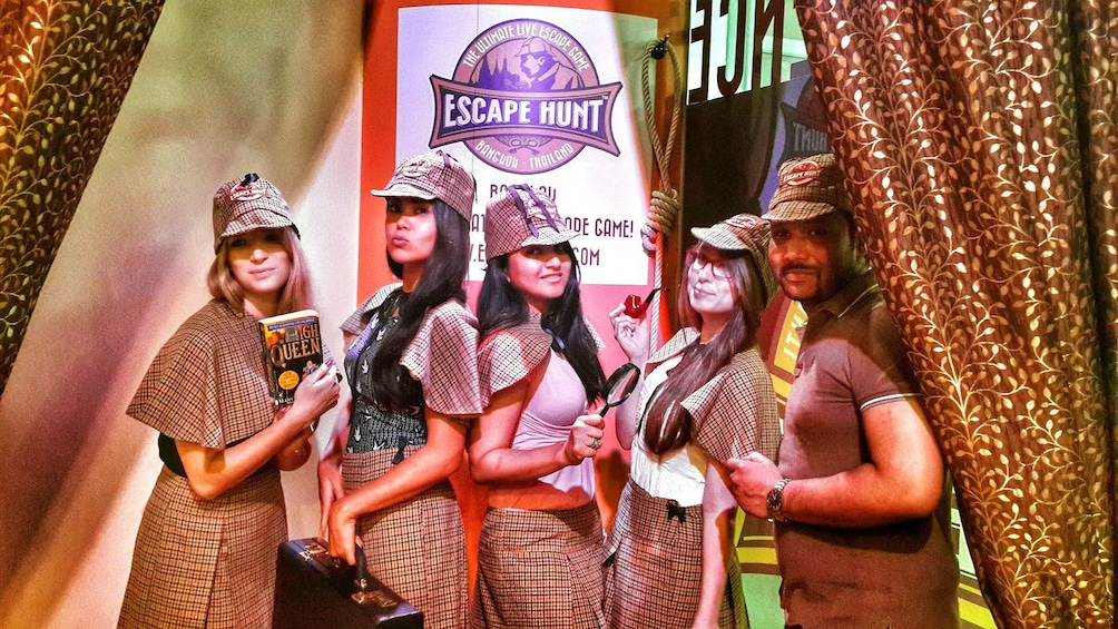 Charger l'élément 2 sur 5. Group posing with props at escape room in Singapore