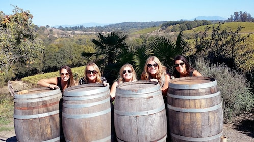 Ladies standing behind wine barrels on the Sonoma Valley Small Group Tour