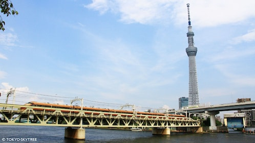 View of Skytree from river with train traveling by in Tokyo
