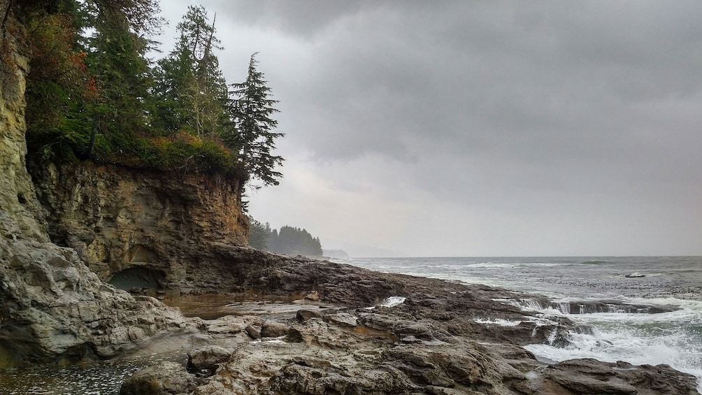 Show item 4 of 5. Rocky beach with cliffs as storm approaches in Port Renfrew