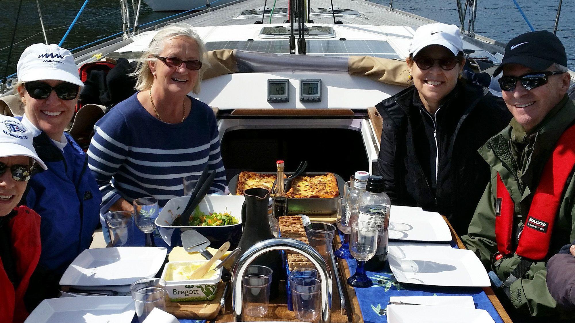 Group having meal on sailboat in Stockholm Archipelago