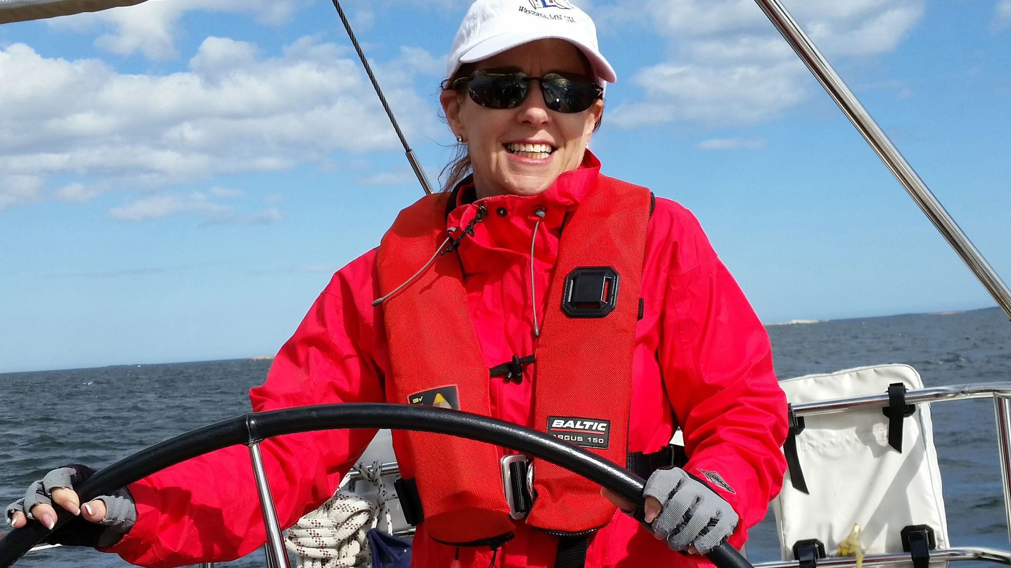 Woman smiles as she pilots sailboat in Stockholm Archipelago