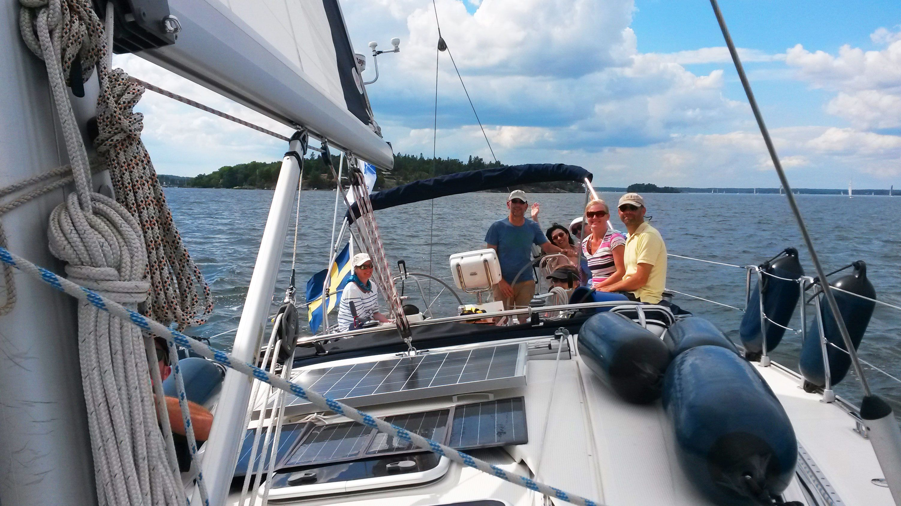 Group sitting at back of sailboat in Stockholm Archipelago