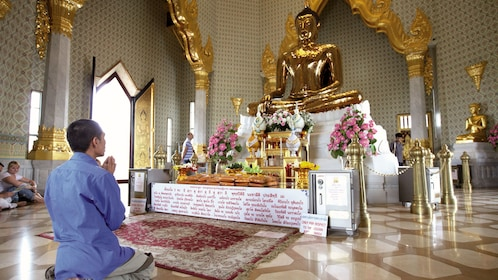 Man praying at a Buddhist shrine in a temple in Bangkok