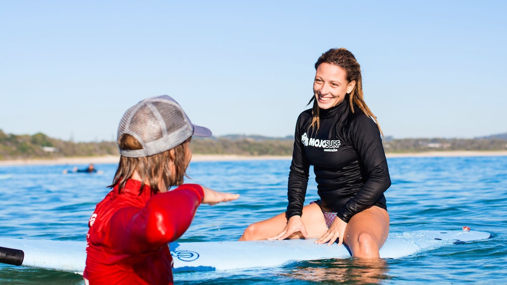 Show item 4 of 5. Surfer with instructor in a surf lesson