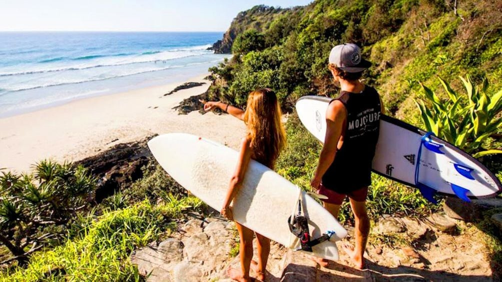 Show item 5 of 5. Two surfers check out the waves from a hill in Australia