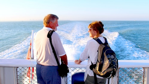 A man and a woman stand at the stern of a boat