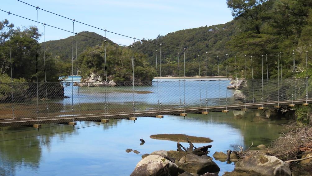 Show item 5 of 5. Cable bridge spanning over water during Abel Tasman Hiking Tour