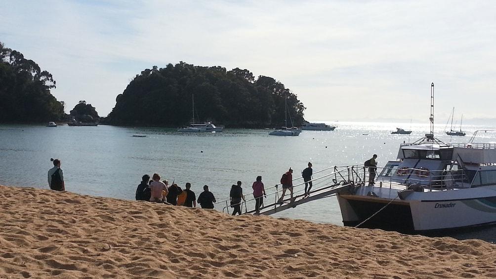 Show item 4 of 5. Cruise boat picking up hikers on Abel Tasman Hiking Tour