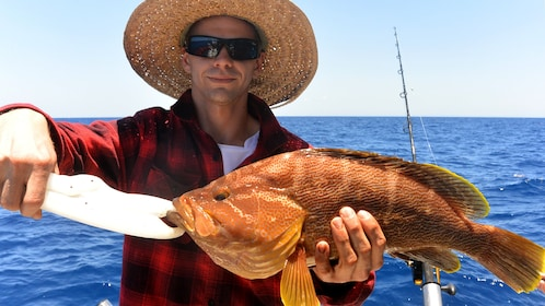 Man with caught fish on a boat in Australia