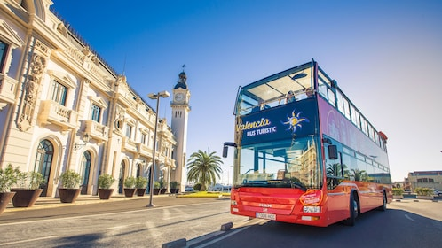 Hop-On Hop-Off tour bus parked outside historical building during tour in Valencia