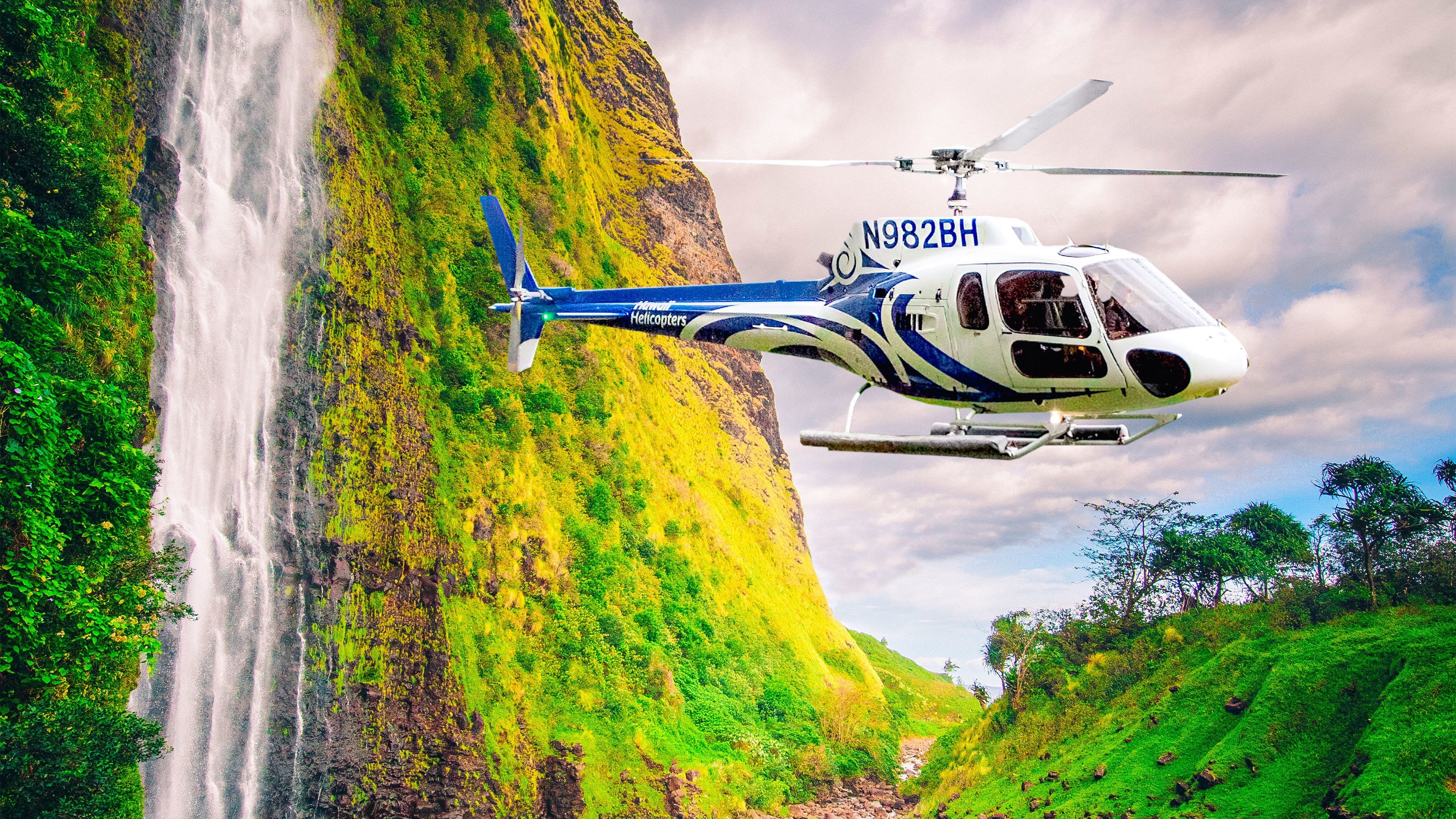 Helicopter flying by a waterfall in Hawaii