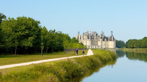 Couple on bicycles with castle in the background in the Loire Valley