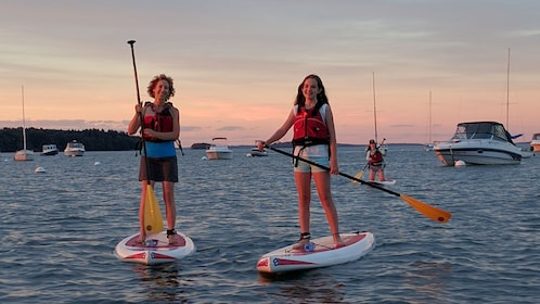 Mother and daughter on stand up paddle boards at sunset in Portland