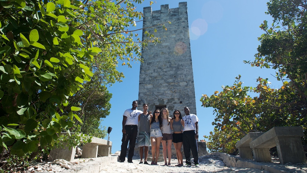 Show item 1 of 5. Tour group stands in front of stone tower in Grand Bahamas