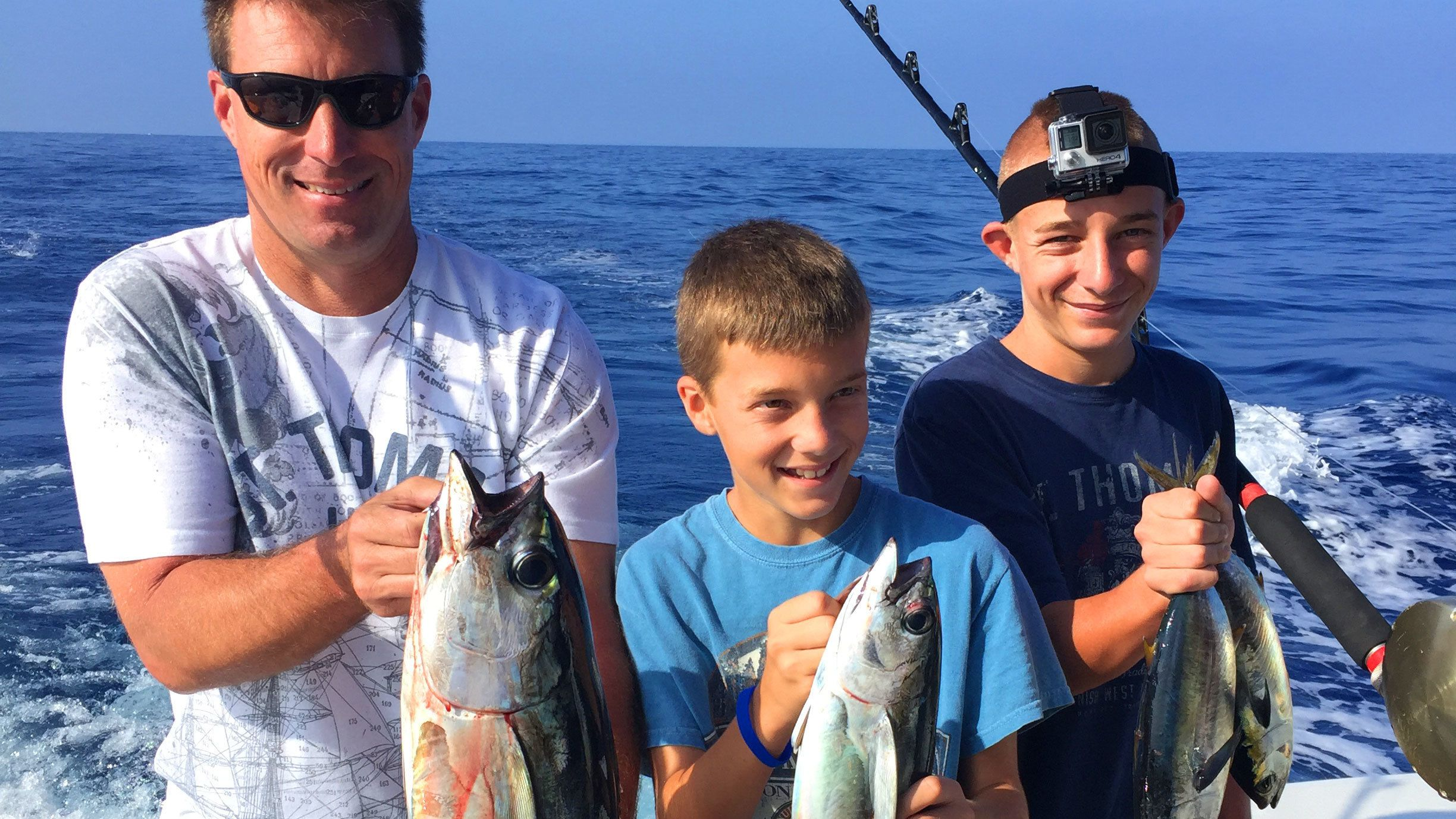 Father and sons holding up catches while in Hawaii