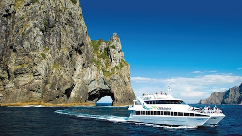 Cruise boat travels through hollowed out rock in New Zealand
