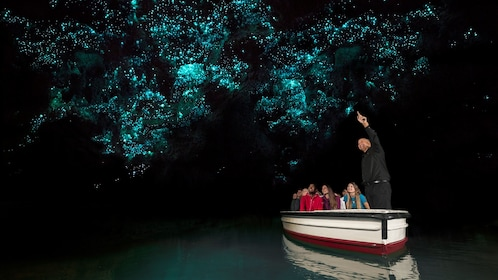 Guide pointing out glowworms on cave ceiling in Waitomo caves in New Zealand