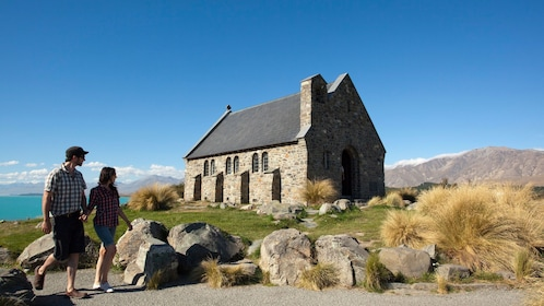 Two hikers pass a stone church in Queenstown Mt.Cook