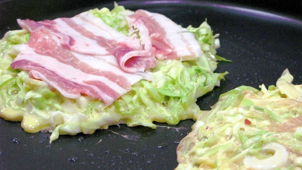 Show item 2 of 6. Tasty Okonomiyaki being fried on a pan at the Osaka Cooking Class in Osaka, Japan