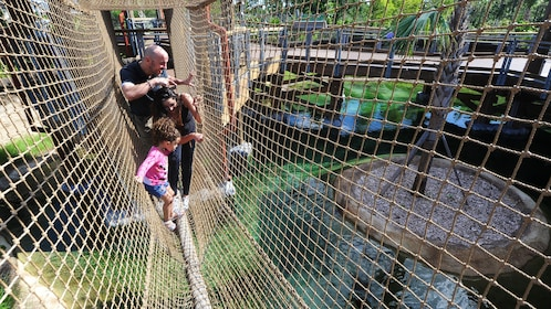 Family climbing across alligator hanging bridge at Zoo Miami