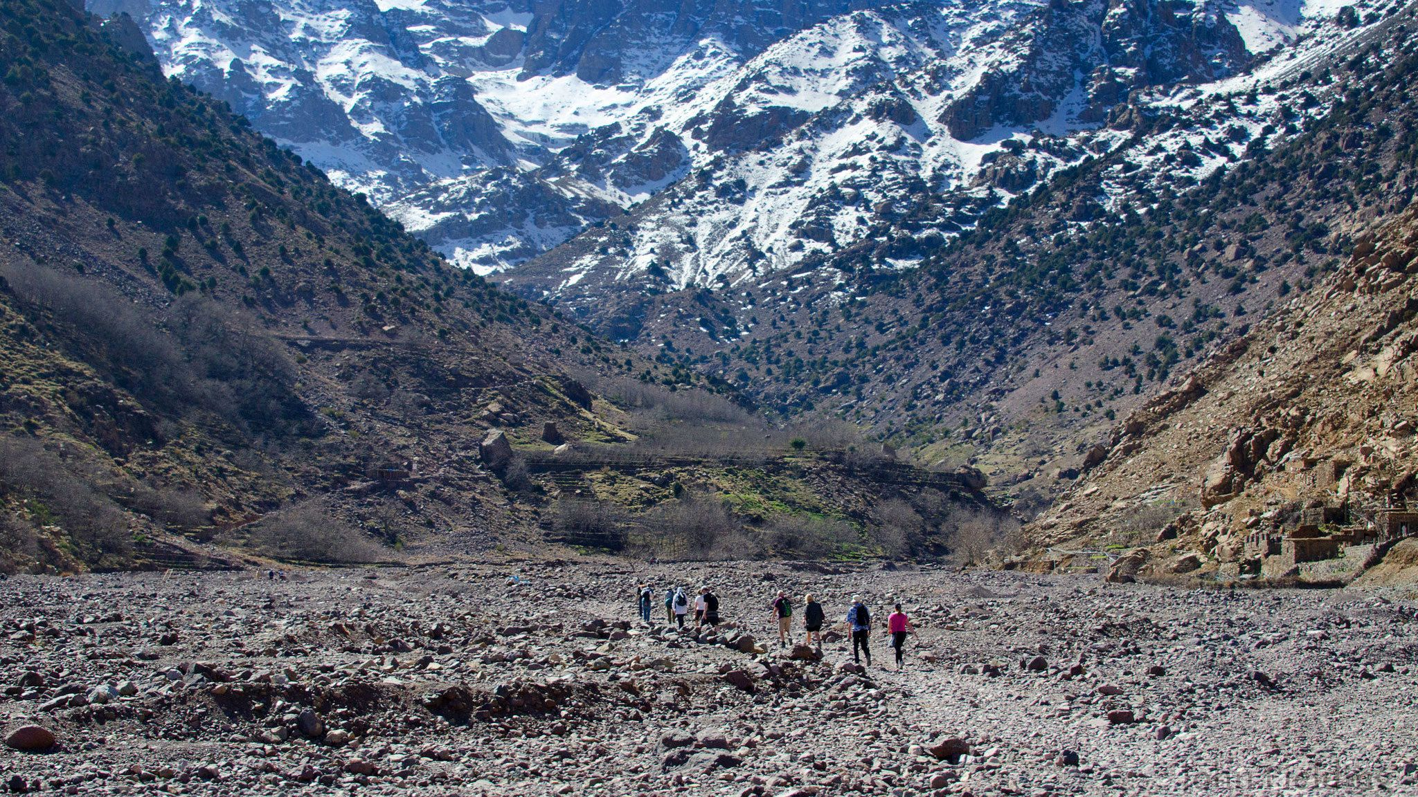 Hikers walking across dry river bed in valley of Atlas Mountains in Marrakech