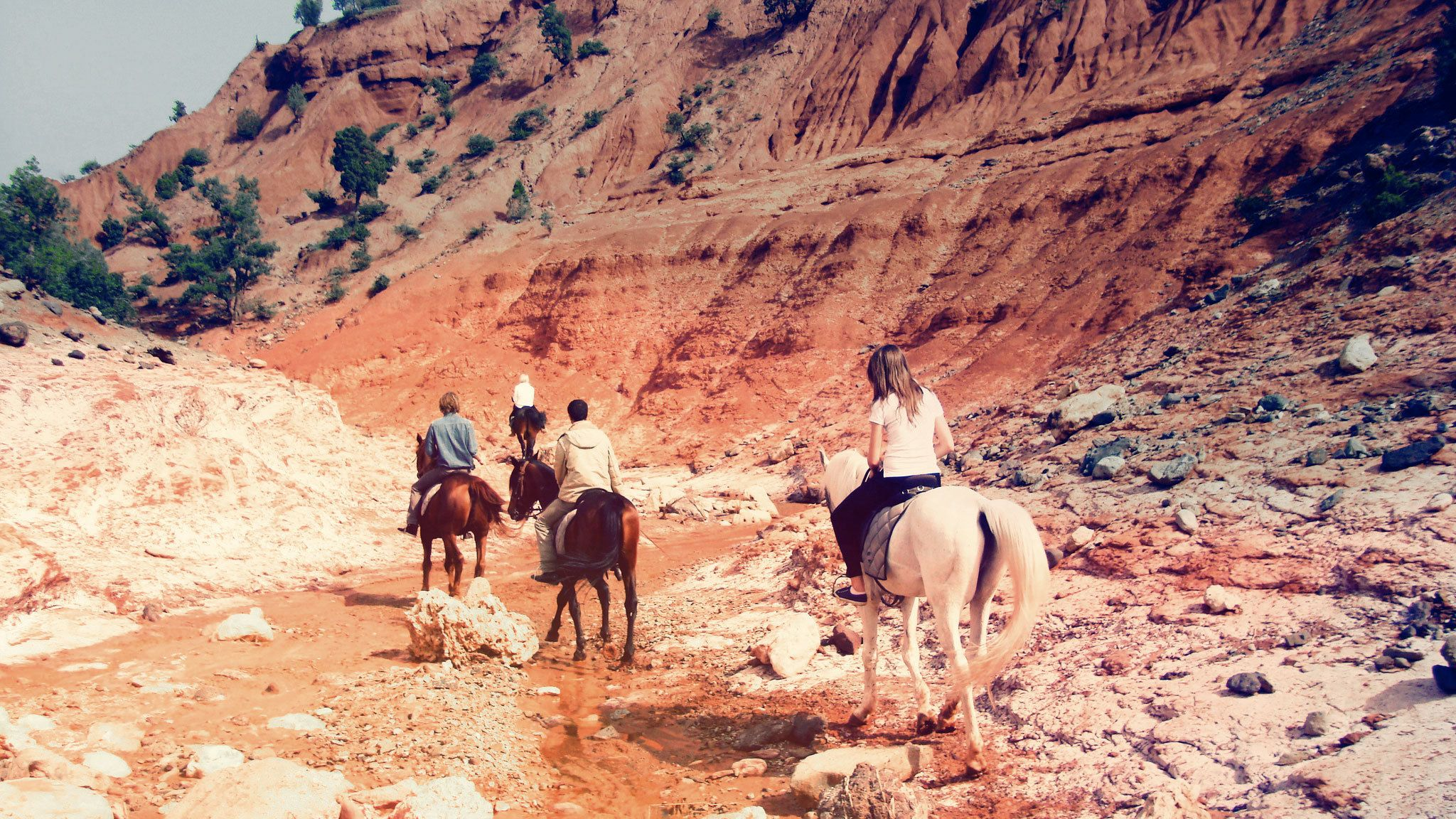 Tourists on horseback riding down creek in Marrakech