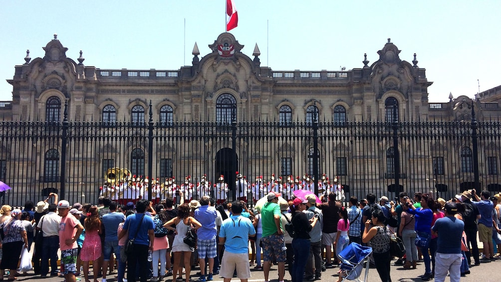 Foto 2 von 5 laden Tourist gather outside of fence to watch changing of guards of Convent of Santo Domingo in Lima