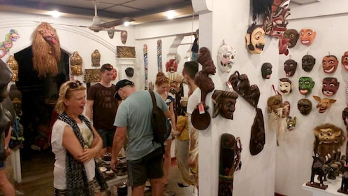 Shopping tourists look at masks in a shop in Sri Lanka