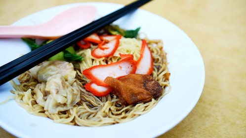 Bowl of noodles and toppings on food tour in Kuala Lumpur
