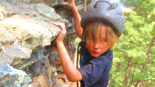 Child climbs a rock face
