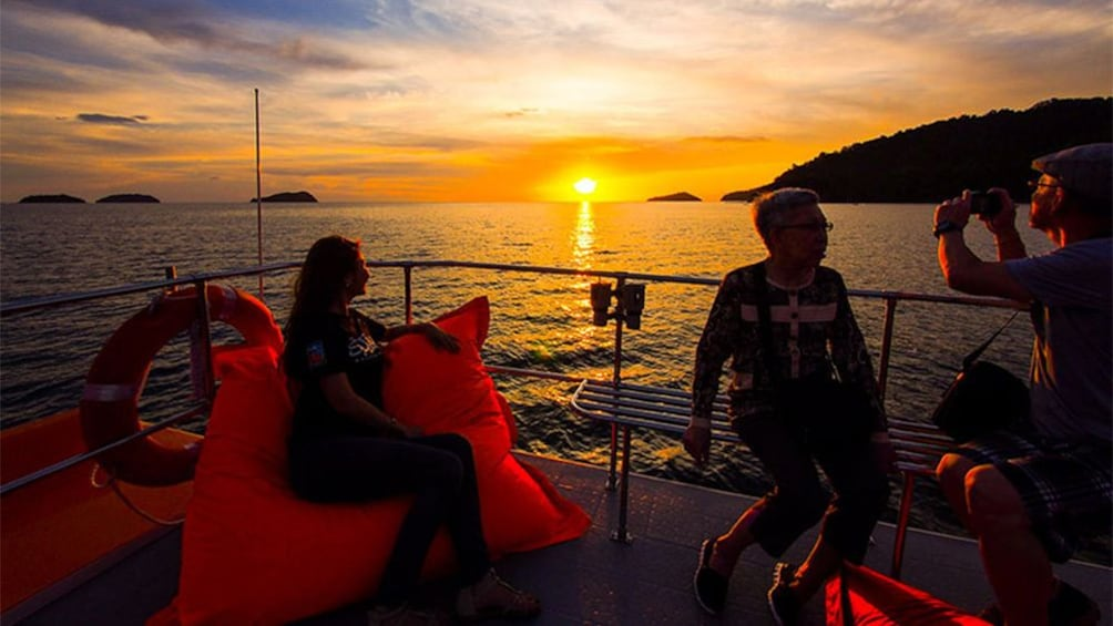 Show item 5 of 5. Boating passengers on the deck at sunset in Kota Kinabalu