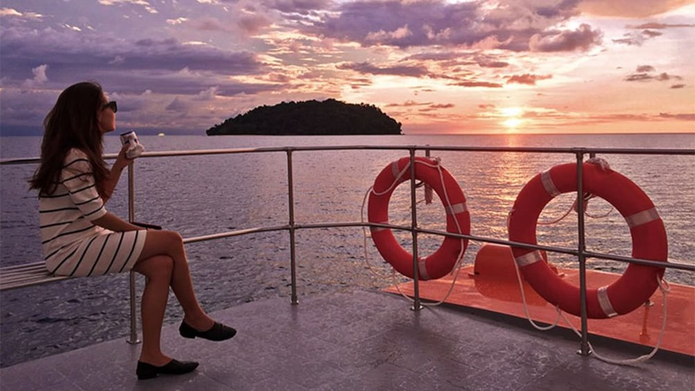 Show item 1 of 5. Woman on the deck of a boat at sunset in Kota Kinabalu