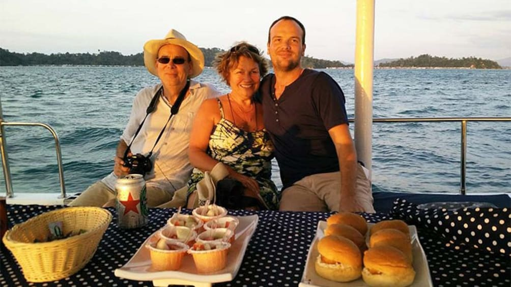Show item 3 of 5. Group with food on a boat at sunset in Kota Kinabalu
