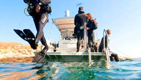 SCUBA divers jump into the water off a boat