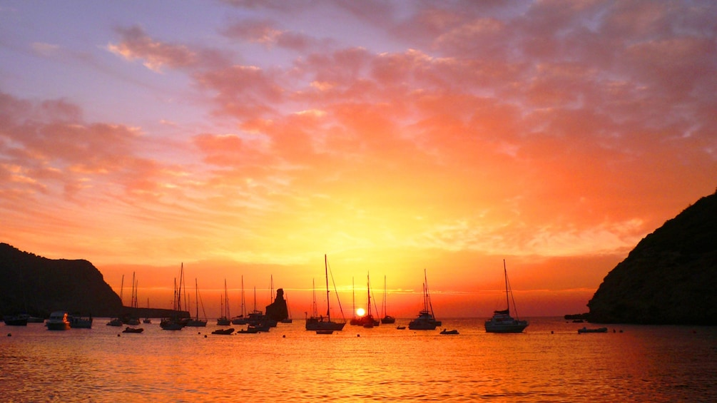 Show item 3 of 4. Sailboats on the horizon at sunset in Ibiza