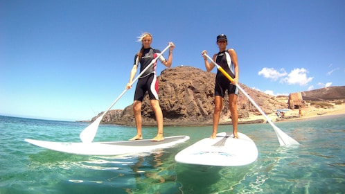 Two women on stand up paddle boards in Ibiza