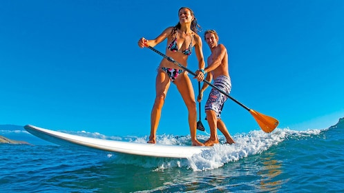 Couple catching small wave on stand up paddle board in Ibiza