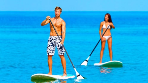 Couple paddling on stand up paddle boards in Ibiza